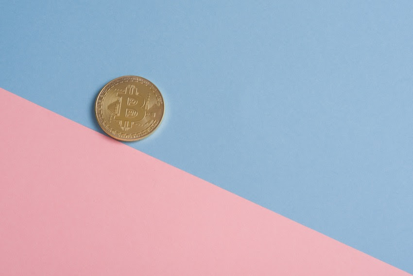 A bitcoin on a pink and blue background